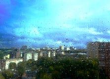 Regendruppels op het venster waarachter de grote stad Stock Fotografie