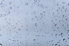 Regendruppels op vensterglas stock afbeelding
