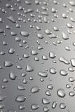 Regendruppels op zilveren oppervlakte Stock Afbeeldingen