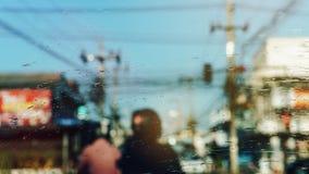 Regendruppeltjes op autowindscherm, in een vaag geblokkeerd verkeer abstracte achtergrond Vuile ruitewisserbladen Slecht weer stock foto
