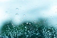 Regendruppeltjes op glas Bomen vage achtergrond Selectieve nadruk Stock Foto's