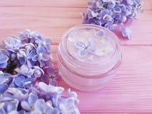Regeneratie van de room de kosmetische organische lilac bloem op een roze houten achtergrond stock afbeelding