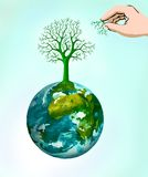Regenerating. Tree symbol rising from the earth and a human hand uniting a missing branch Royalty Free Stock Photo