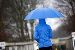 Regengang met zijn paraplu en regenjas Royalty-vrije Stock Afbeeldingen