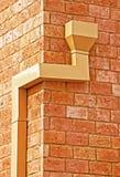 Regengosse auf einer Backsteinmauer Stockfoto
