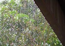 Regenrückgänge fallen ununterbrochen vom Dach mit Unschärfegrünnatur stockfotografie