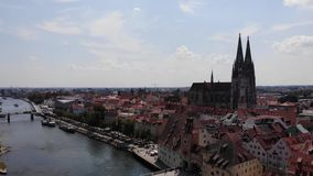 Regensburg Cathedral and Old Town architecture, people on Stone Bridge. Aerial view, technique of smooth descent down stock video