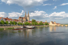 Regensburg in the morning light on a summer day with the promenade the Cathedral and the stone bridge Stock Photography