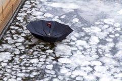Regenschirm auf einem Eis von Stadtfluß oder -see lizenzfreies stockfoto