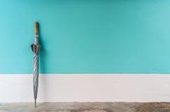 Regenschirm auf Zementboden mit Pastellwandhintergrund Lizenzfreie Stockfotos