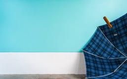 Regenschirm auf Zementboden mit Pastellwandhintergrund Stockfoto
