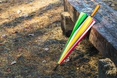 Regenschirm, der auf einer Bank im Herbst Park liegt lizenzfreie stockbilder