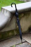 Regenschirm, der das konkrete Geländer bereitsteht Lizenzfreies Stockbild