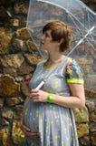 Regenschirm der schwangeren Frau der Junge Lizenzfreies Stockfoto