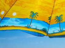 Regenschirm mit Palmen gegen den blauen Himmel Lizenzfreies Stockfoto