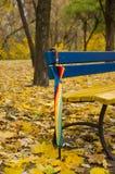 Regenschirm nahe einer Bank im Herbstpark Stockbild