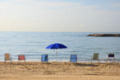 Regenschirm und bunte Stühle auf dem Strand Stockfotografie