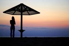 Regenschirm und das Mädchen auf einem Strand. Abend Lizenzfreies Stockfoto
