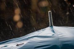 Regenschirm und harte Regentropfen, zum herauf Hintergrund zu schließen Stockfotografie