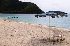 Regenschirm und Stuhl auf Strand Stockbilder