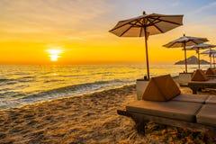 Regenschirm und Stuhl mit Kissen um schöne Landschaft des Strandes und des Meeres lizenzfreie stockfotografie