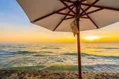 Regenschirm und Stuhl mit Kissen um schöne Landschaft des Strandes und des Meeres lizenzfreie stockfotos