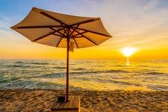 Regenschirm und Stuhl mit Kissen um schöne Landschaft des Strandes und des Meeres stockfoto