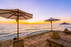 Regenschirm und Stuhl mit Kissen um schöne Landschaft des Strandes und des Meeres stockbilder