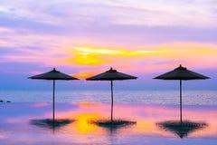 Regenschirm und Stuhl um Ozeanstrand des Swimmingpools neary Seezur Sonnenaufgang- oder Sonnenuntergangzeit lizenzfreies stockfoto