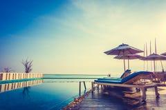Regenschirm und Stuhl um Swimmingpool lizenzfreies stockfoto