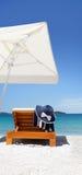 Regenschirm und sunbed auf dem Strand mit Hut und Tuch Lizenzfreie Stockfotos