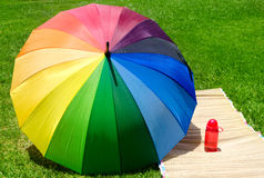 Regenschirm- und Wasserflasche auf dem Gras Stockfotos