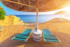 Regenschirm und zwei leere deckchairs auf dem Ufersand setzen auf den Strand Lizenzfreie Stockfotografie