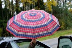 Regenschirm vom Auto, setzte sich heraus in der Hand stockfotografie