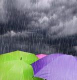 Regenschirme in den regnerischen Sturm-Wolken