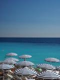 Regenschirme setzen in Nizza, Frankreich das französische Riviera auf den Strand Lizenzfreie Stockfotografie