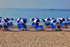 Sandy-Strand mit blauen umbrellasand Stühlen Lizenzfreies Stockbild