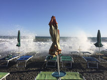 Regenschirme und Strandstühle während der rauen Meere Stockfoto
