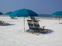 Regenschirme und Stuhlstühle auf Strand Stockfoto