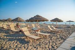 Regenschirme und Wagenaufenthaltsräume auf dem Strand von Rimini in Italien Stockfotos