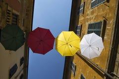 Regenschirme von verschiedenen Farben über der Straße mit blauem Himmel als Hintergrund Lizenzfreie Stockfotos