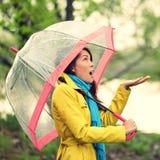 Regenschirmfrau im Herbst aufgeregt unter Regen Stockfotos