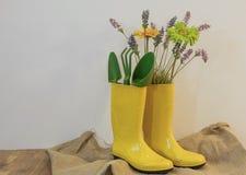 Regenstiefel mit Gartenarbeitausrüstungs- und -frühlingsblumen auf dem eco Hintergrund vom Sackleinen stockfoto