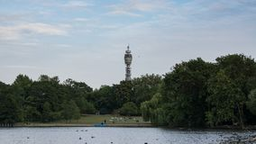 Regenter ` s Park in London, England mit See im Vordergrund und dem BT-Turm hinter Bäumen im Hintergrund lizenzfreie stockbilder