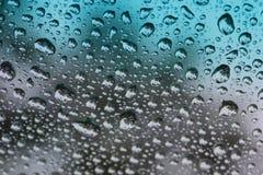 Regentropfen auf abgetöntem Glas. Stockbild