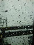 Regentropfen auf Autoglas mit einem grauen Himmelhintergrund Stockbilder