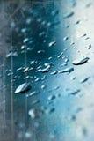 Regentropfen auf blauem Fenster Stockbilder