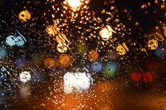 Regentropfen auf dem Fenster Bokeh-Nachtstadt Lizenzfreie Stockfotografie