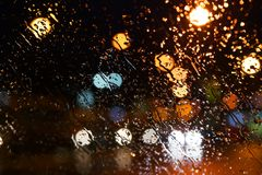Regentropfen auf dem Fenster Bokeh-Nachtstadt lizenzfreies stockfoto