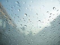 Regentropfen auf dem Glas des Autos mit undeutlichem bewölktem Himmel und Dorf Lizenzfreie Stockbilder